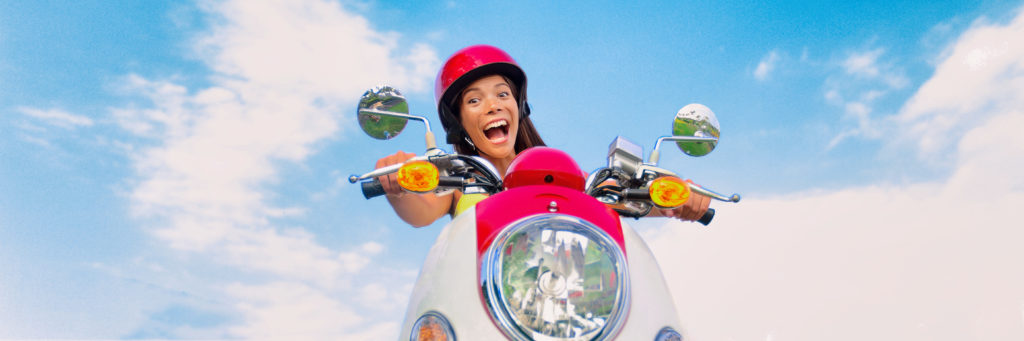 Travel fun funny tourist carefree driving scooter on summer road trip. Screaming Asian girl playful laughing riding motorcycle. Panoramic banner.